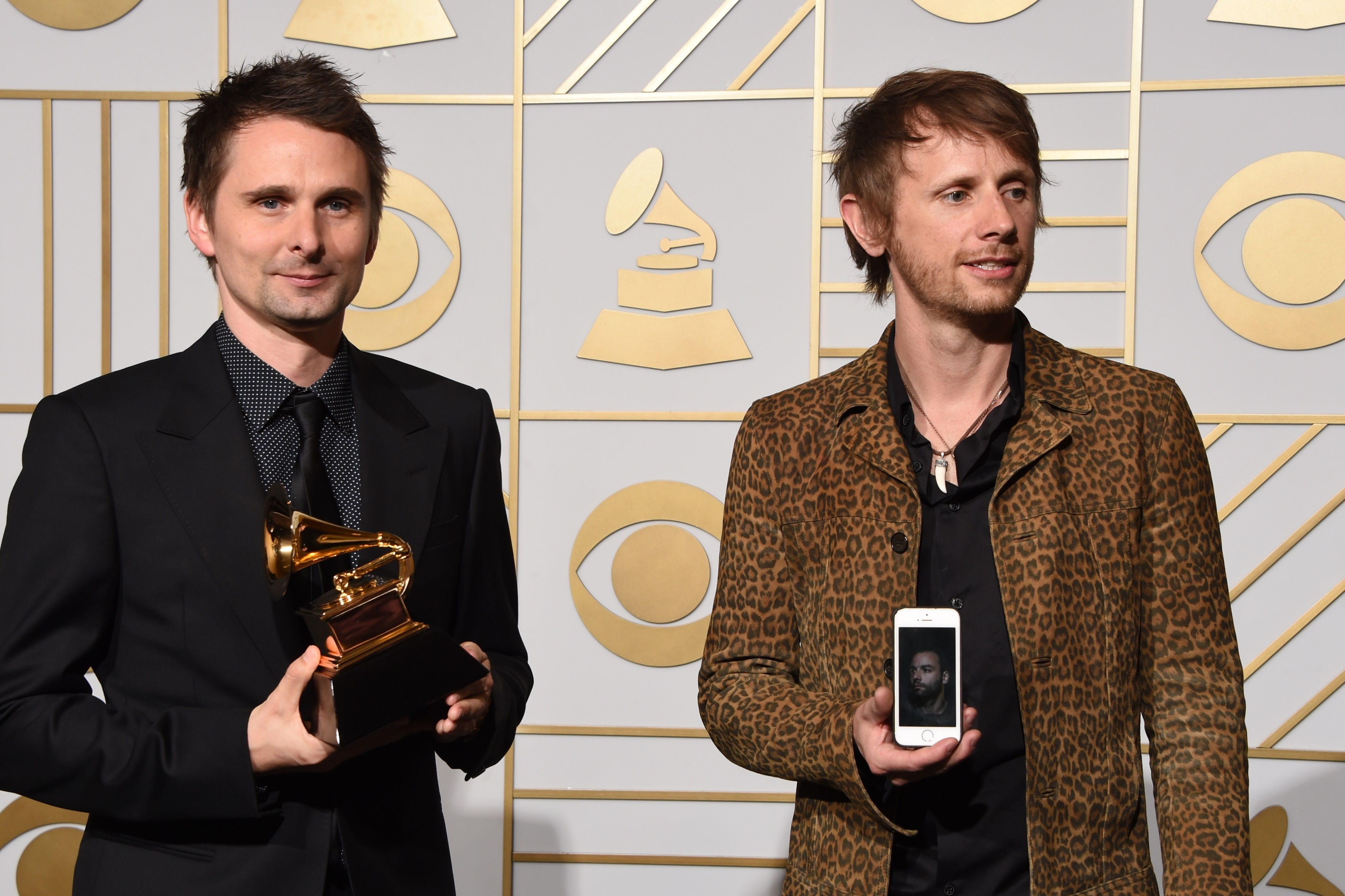 """Muse pose in the press room with their Best Rock Album trophy for """"Drone"""" during the 58th Annual Grammy Music Awards in Los Angeles on February 15, 2016. AFP PHOTO / Mark RALSTON / AFP / MARK RALSTON"""