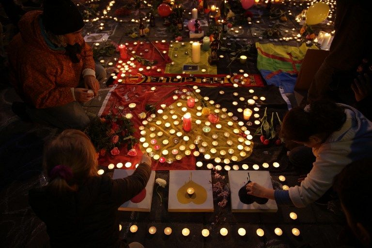 People light candles in tribute to victims at a makeshift memorial in front of the stock exchange at the Place de la Bourse (Beursplein) in Brussels on March 22, 2016, following triple bomb attacks in the Belgian capital that killed about 35 people and left more than 200 people wounded. A series of explosions claimed by the Islamic State group ripped through Brussels airport and a metro train on March 22, killing around 35 people in the latest attacks to bring bloody carnage to the heart of Europe. AFP PHOTO / KENZO TRIBOUILLARD / AFP / KENZO TRIBOUILLARD